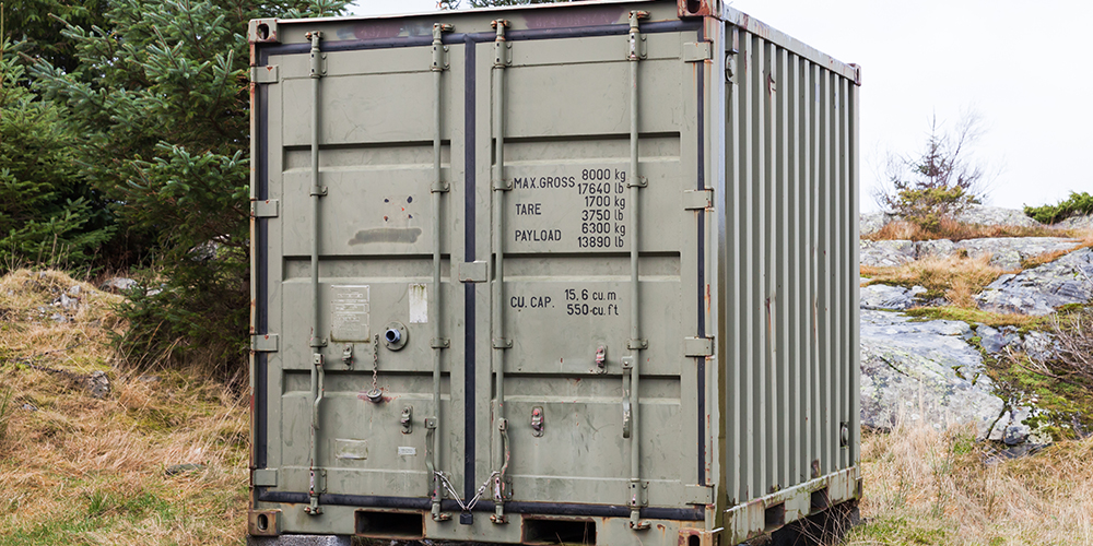 Military green cargo container stands on grass, industrial shipping equipment